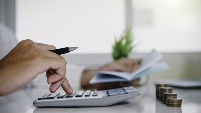 asian man working with calculator to calculate numbers. expenses calculator, payments costs with paper notes, payments table. Financial and Installment payment concept. Saving concept - Image