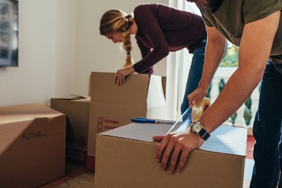 Couple packing their items in packing boxes